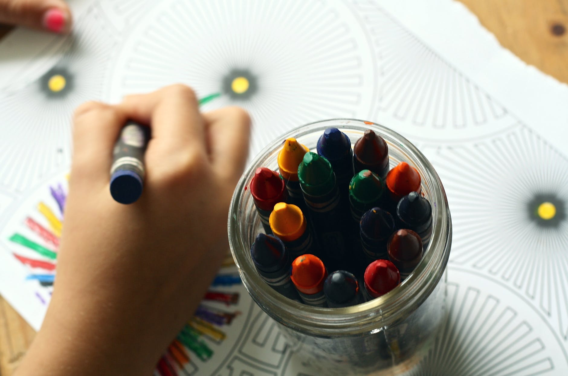 child's hand holding a crayon coloring on a piece of paper