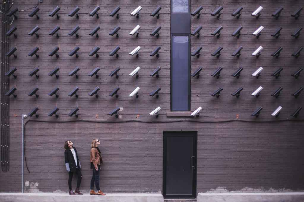 two people stand in front of a wall with rows and rows of security cameras, spaced closely together